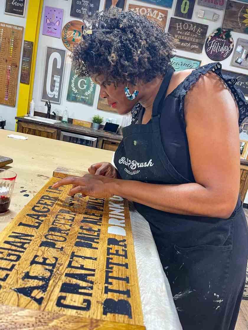 Woman making DIY Wood Board at Board and Brush