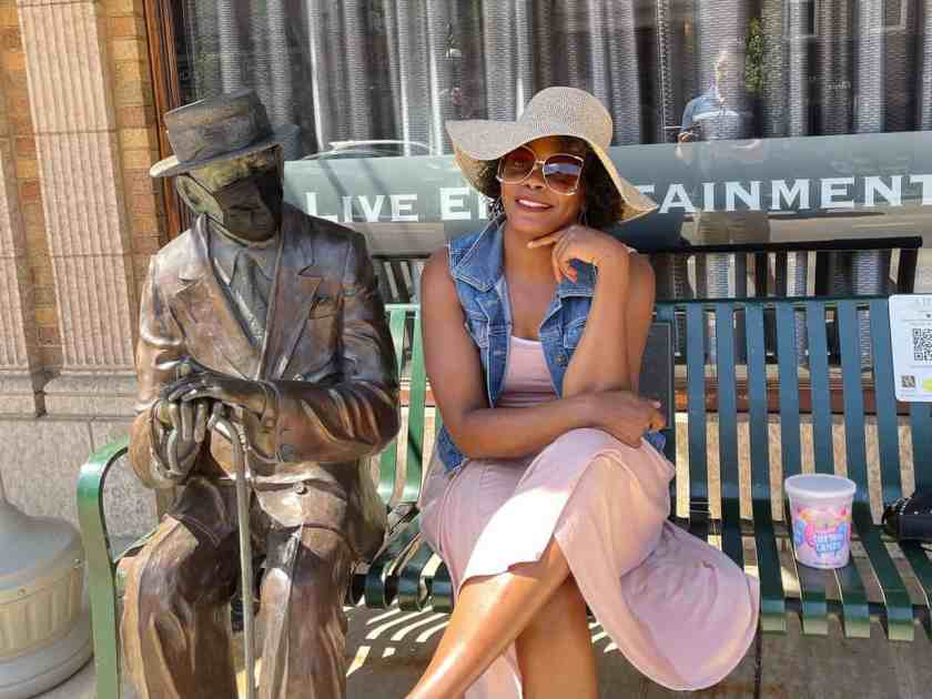 Woman smiling sitting on a bench in downtown St. Charles, Illinois