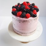 Three layers of dark chocolate cake stuffed with Nutella, frosted with triple berry Swiss meringue buttercream and topped with a mountain of blueberries, raspberries, and blackberries.