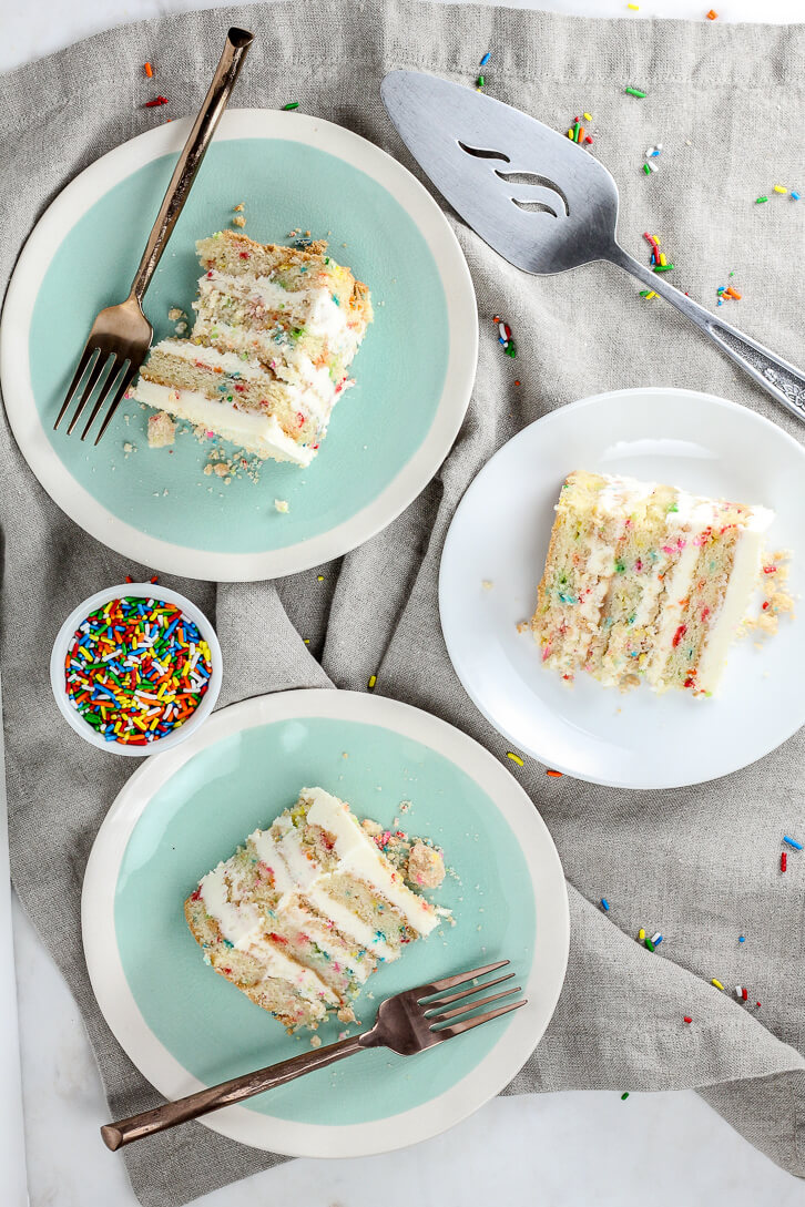 Slices of Milk Bar Birthday Cake studded with rainbow sprinkles