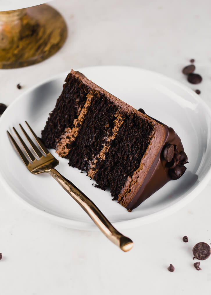A slice of gluten-free chocolate cake with three layers and chocolate fudge frosting