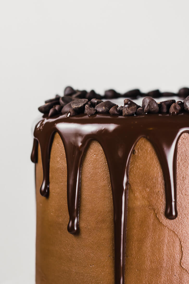 As a simple decoration for this gluten-free chocolate cake, a ring of triple chocolate chips sits on top of a rich, dark chocolate ganache