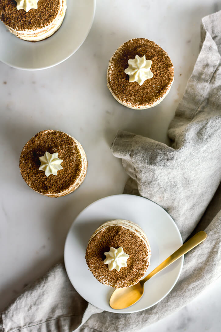Individual-sized tea tiramisu dusted with cocoa powder and topped with mascarpone cream