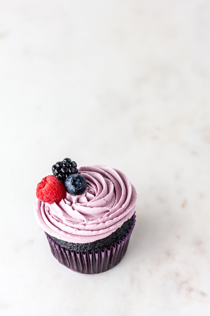 A single Nutella stuffed dark chocolate cupcake frosted with a swirl of triple berry Swiss meringue buttercream and topped with a raspberry, blueberry, and blackberry.