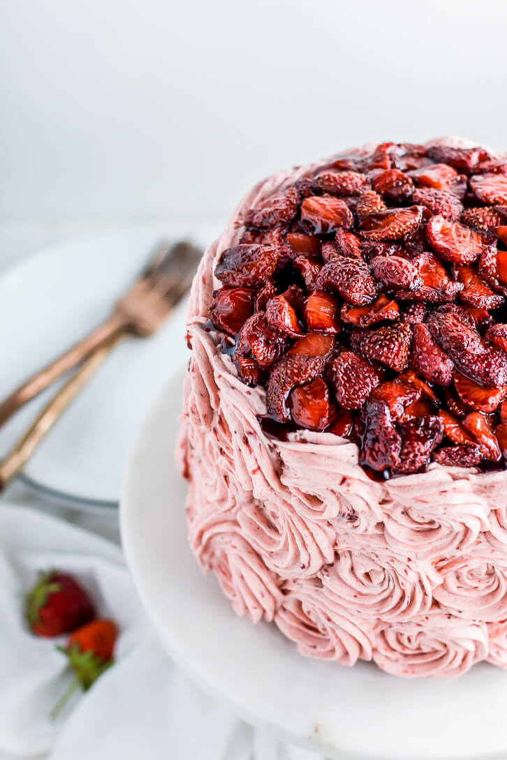 Three layers of vanilla bean cake, frosted with balsamic roasted strawberry buttercream and topped with a mountain of balsamic roasted strawberries.