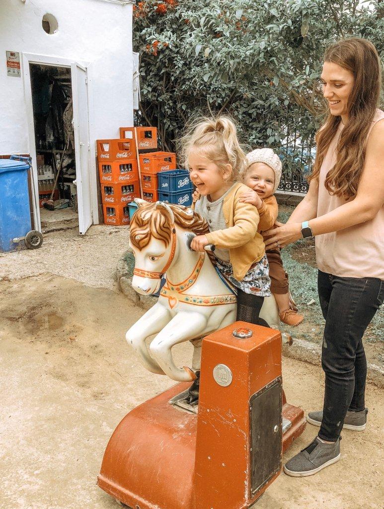 two little girls riding a mechanical horse