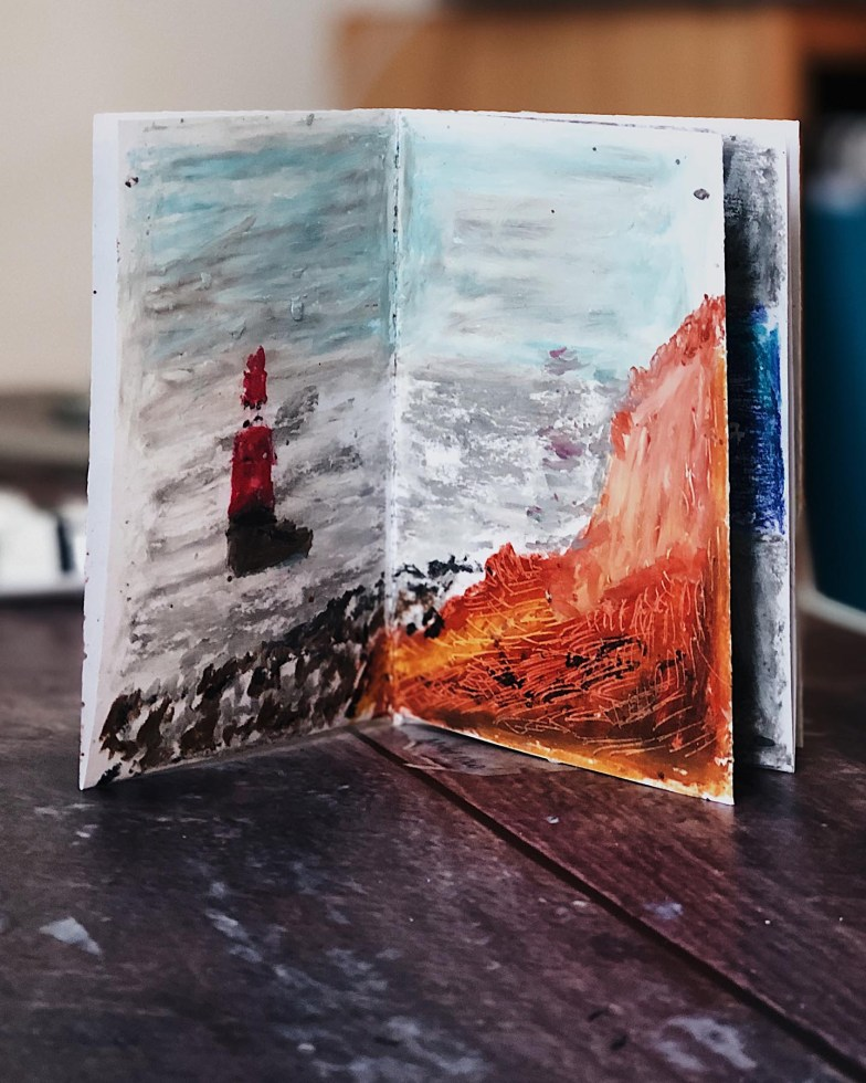 A small zine standing vertical depicting a lighthouse in oil pastel