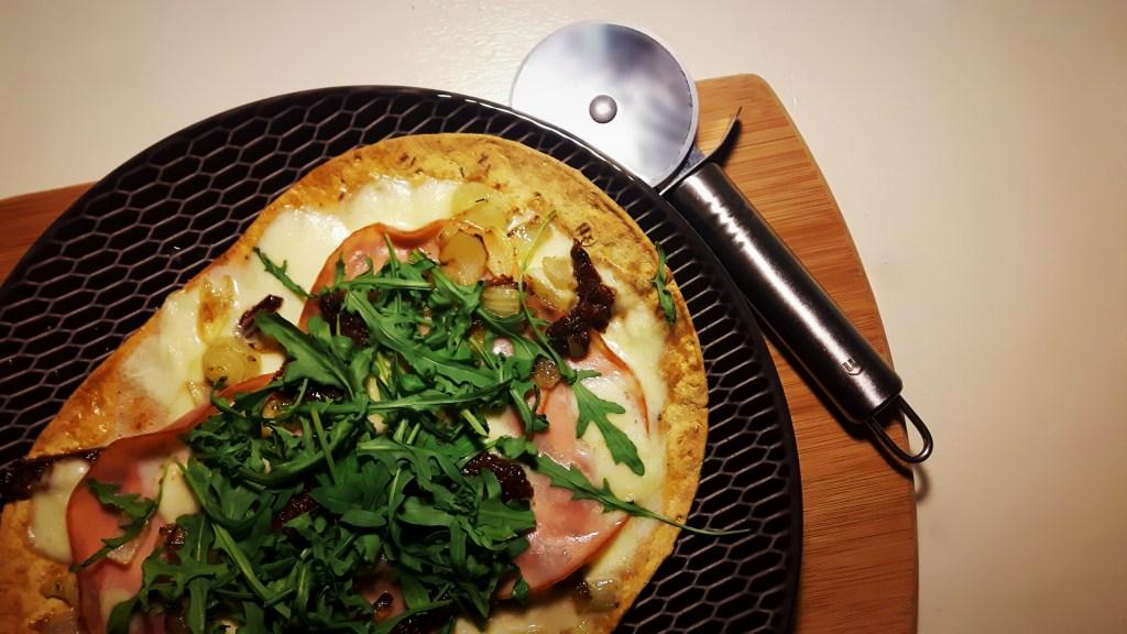 Koolhydraatarme pizza met ham, mozzarella, gekarameliseerde ui, zongedroogde tomaat en rucola