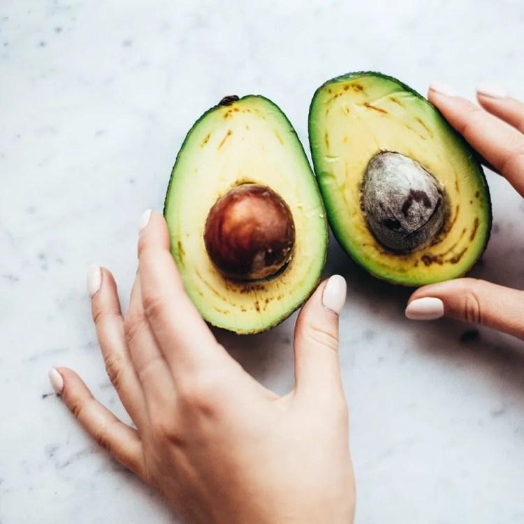 person holding sliced avocado