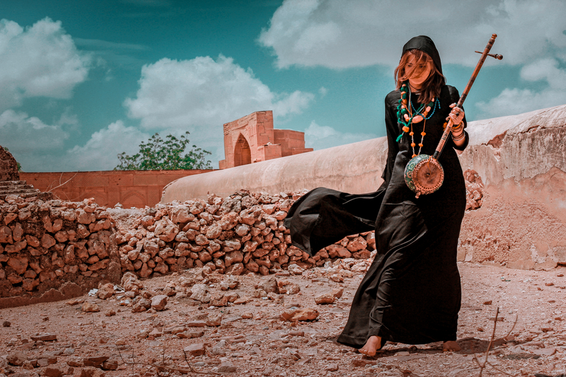 Girl as a malang (wandering mystic) with musical instrument at a shrine in Sindh, Pakistan 10/06/2015