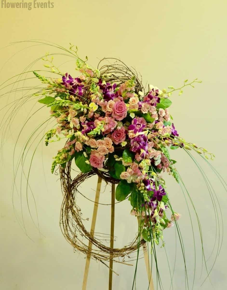 A standing wreath of pinks and purples, snapdragons, orchids, roses and spray roses