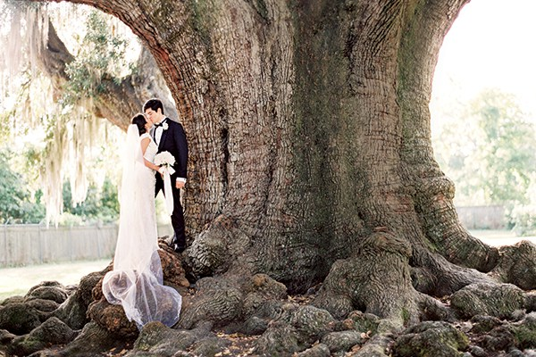 Before the ceremony, the bride and groom pose for pictures underneath a massive oak tree in New Orleans' Audubon Park.
