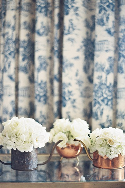 The bride scoured Gulf Coast thrift stores for antique copper watering cans, which were filled with white roses and hydrangeas for the flower girls.