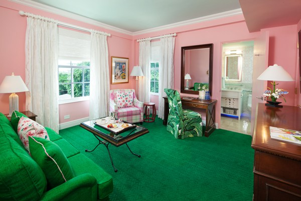 A guest room sitting area preppy in pink and green. Photo courtesy of Colony Hotel