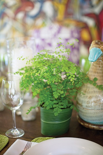 Liza decorates her table with green ferns in pots cleverly wrapped in ginger lily leaves from her garden.