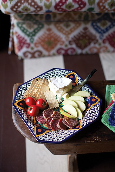 Hors d'oeuvres are as simple as fruit, cheese, crackers, and summer sausage on a majolica serving plate.