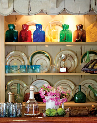 Fresh-cut pink bougainvillea in a white ceramic pitcher pairs well with the lime and turquoise on the bar.
