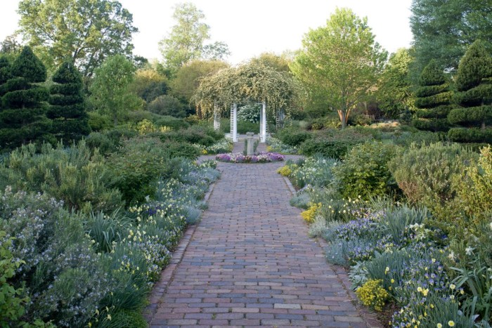 Photo of a brick walkway through through a Virginia garden on the 86th Historic Garden Week Tour in 2019, leading to flower covered pergola