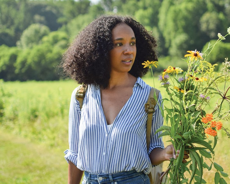 The artist stands in a green field dressed in jeans and a blue-and-white stripe blouse and a backpack.