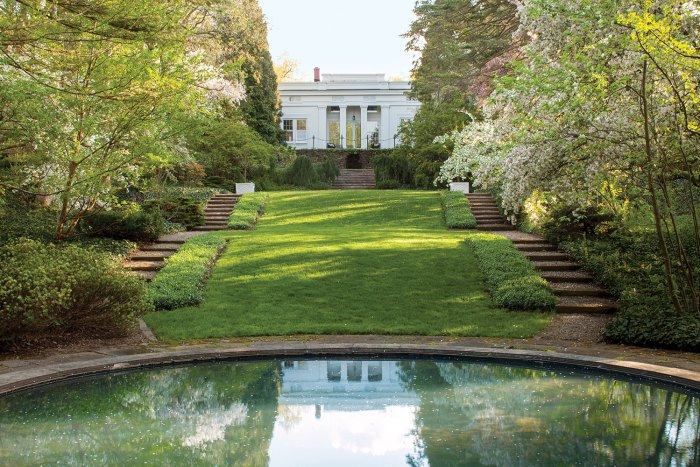 Melissa McGrain's Greek Revival home overlooks a lawn and circular pond. The historic Fletcher Steel landscape design features woodlands and a set of terraced stairs on either side of the house and lawn.