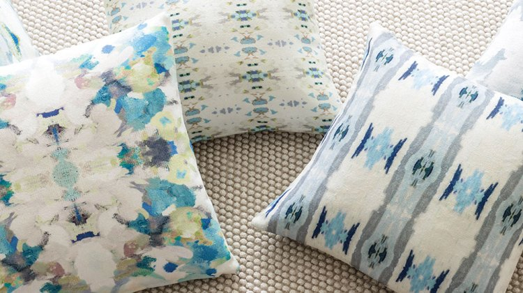 Four throw pillows in various airy patterns featuring shades of blue