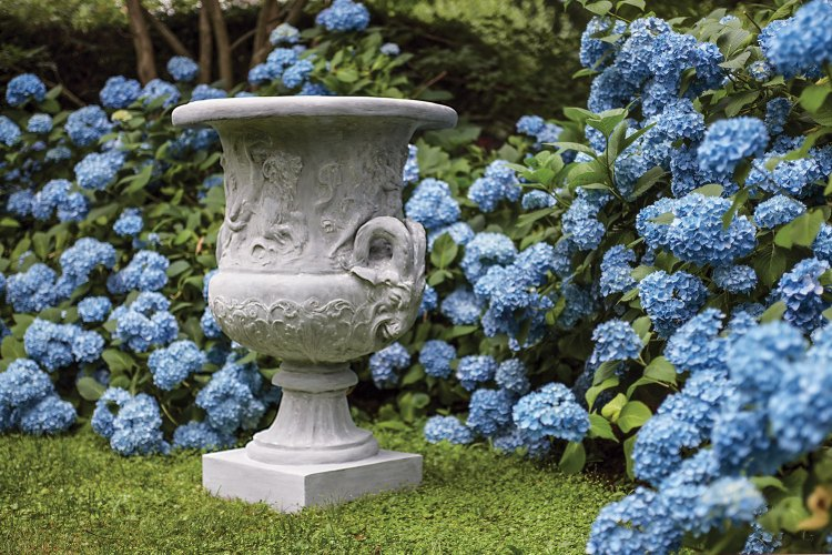 The Pennoyer Newman urn sits on a green lawn surrounded by blue hydrangeas.