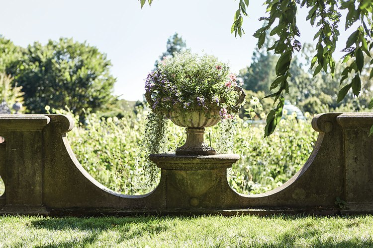 The photo shows one of the three Pennoyer Newman urns overflows with plants. The wall dips low on either side of the urn, giving a peek inside the garden.