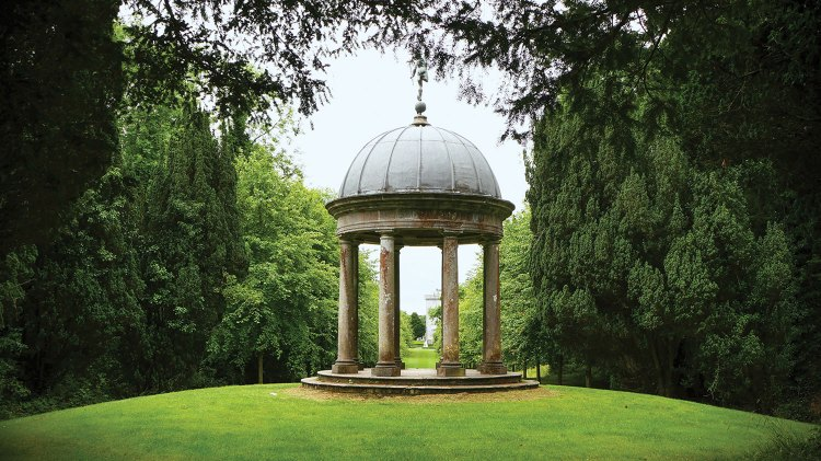 The Temple of Mercury in Ireland features a dome roof and a circular colonnade. It sits on a low mound of bright green lawn. Lush trees surround it.