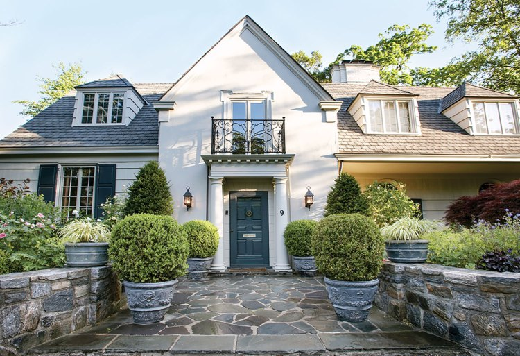 Planters filled with boxwoods and grasses line a wide stone path, flanked by low, curved stone walls on either side, leading to the entrance of a white home. The home features dormer windows on the second floor and a two-story entrance with a black wrought iron balcony off the window above the door. Various flowering plants fill the yard.