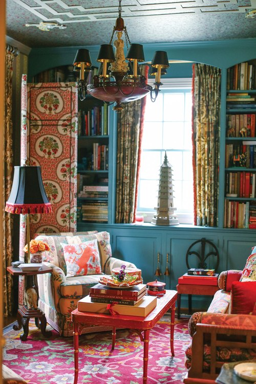 The cozy Asian-inspired den features a bright oriental rug, a red laquor coffee table, upholstery boasting rich hues and patterns, and wall bookshelf/cabinetry painted a dusty blue. A small pagoda tower sits in the window.