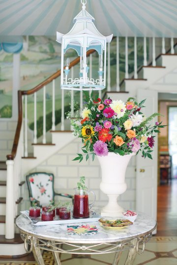 A round marble-top table with an elegant metal base holds a vase of flowers and tray of cocktails to greet party guests in the cottage's foyer