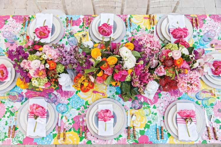The long table is set with bamboo-handled flatware, simple white and blue plates, white scallop-edged napkins with a band of 3 pink stripes, and a pink peony atop each setting.