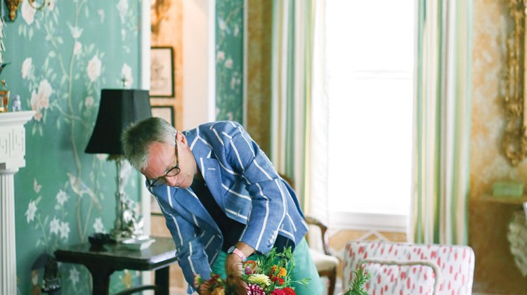 John Loecke stands over the coffee table. The arrangement features colorful zinnias in a small white porcelain urn