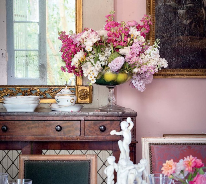A sideboard displays a large floral arrangement of pink, white and pale purple blooms in a glass pedestal bowl. Apples placed in the bowl mask the stems.