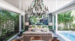One of the home's many indoor-outdoor living spaces, the open-air living room includes the dining table and chandelier, two sofas facing each other, and, on the back wall, a large floral painting by Marcella Kaspar.