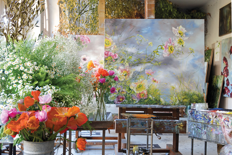 Vases of bright pink and orange flowers alongside paintings in Claire Basler's studio