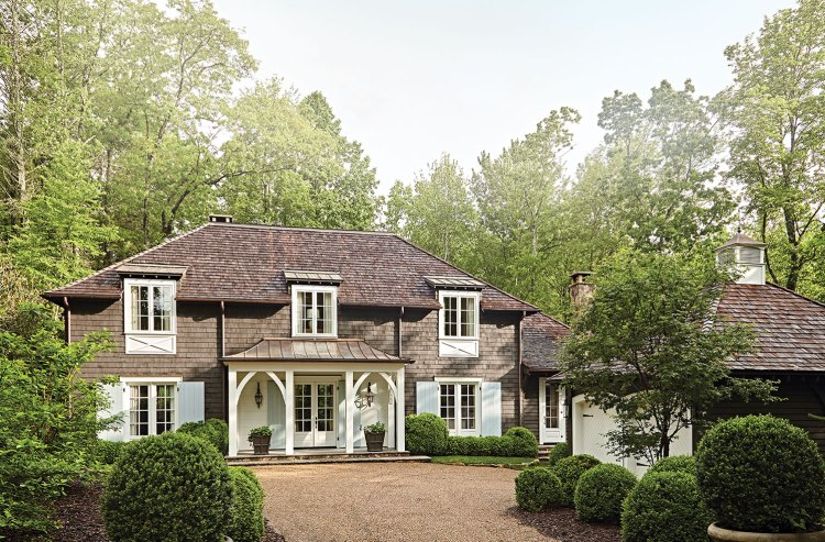 Front elevation of a mountain house designed by architect Shannon Hargrove in Cashiers, North Carolina, with a detached two-car garage with stable-style doors and a pea gravel driveway. The landscape by Bellwether Landscape Architects features boxwoods in a variety of sizes, mulch, and only small areas of grass, fitting in with many trees that surround the mountain property