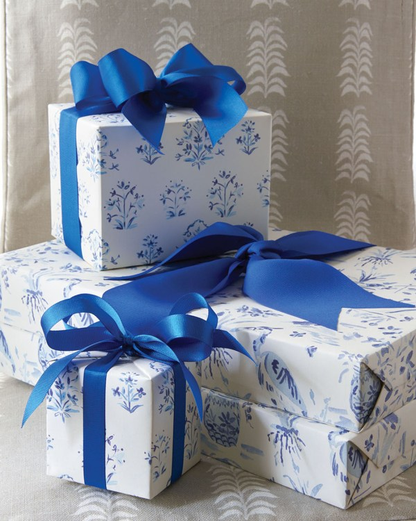 A stack of wrapped presents tied with blue ribbon
