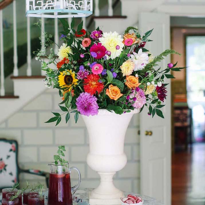 Large zinnia flower arrangement in a white urn