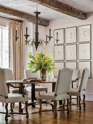 Other mountain house decorating ideas to take away from this Francie Hargrove dining room include floor-to-ceiling curtain panels in a large gingham print in natural white and khaki. On the table is a loose, rustic floral arrangement of branches, including dogwood blooms, oak leaves, as well as a candle in a Simon Pearce hurricane. The framed pressed flowers are hung in a large grid of 9 on one wall.