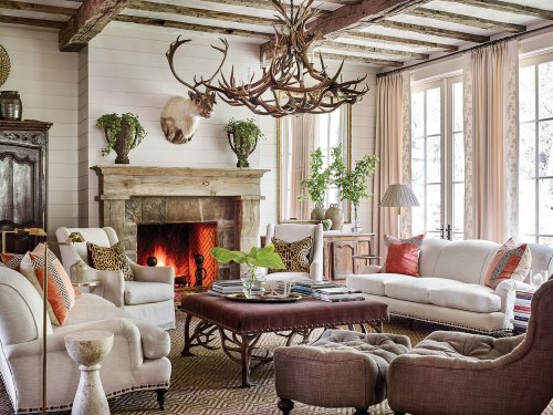 Inspired by the grandeur of French limestone mantels, she created a wooden version from pieces of mismatched timber inadvertently included in a shipment of reclaimed beams. The fieldstone surround supports the weight of the mantel and corrals all of the room's neutral hues. Other mountain house design ideas from this scene include a large chandelier made of deer antlers, a pair of sofas and side chairs upholstered in a soft white fabric, and throw pillows, including (on each sofa) a pair of pillows in strié coral velvet inset with a Greek key pattern, as well as (on each side chair) an leopard-print linen pillow. One tufted, curved accent chair with a matching ottoman is upholstered in a dark brown linen-type fabric. At the center of the seating area is a large square coffee table upholstered in a dark, rich fabric. A neutral patterned area rug grounds the seating area. Arrangements of simple cut greenery on the mantel, coffee table, and console add a punch of color. Swing-arm floor lamps and stacks of books invite one to sit and read by the fire. Soft white shiplap walls and curtains keep the room light and airy.