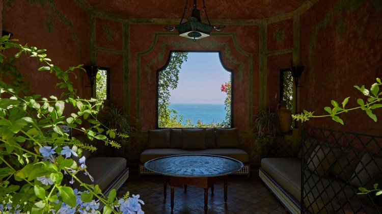 An ocean view framed by an ornate, but simply furnished sitting room with banquets on three walls around a low circular table