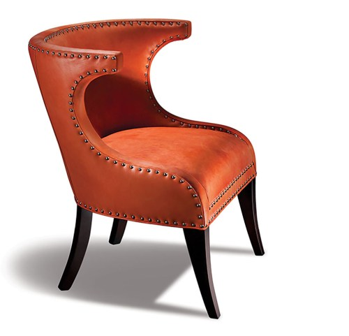 "chair featuring orange ""chrysanthemum-colored' leather upholstery and dramatic curving lines accentuated by grommet outline"