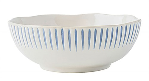 Rustic white porcelain bowl with linear patter of vertical blue lines decorating outer rimm