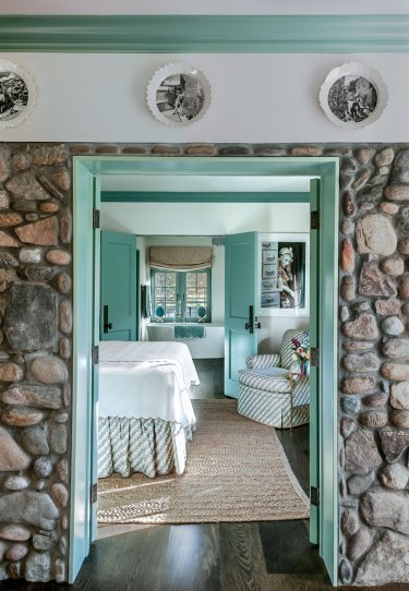 Stone wall with aqua trim leading to a bedroom