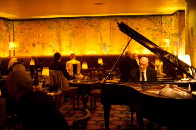 A piano player performs in a dimly lit, scenic wallpaper-wrapped dining area of Bemelmans Bar in New York City