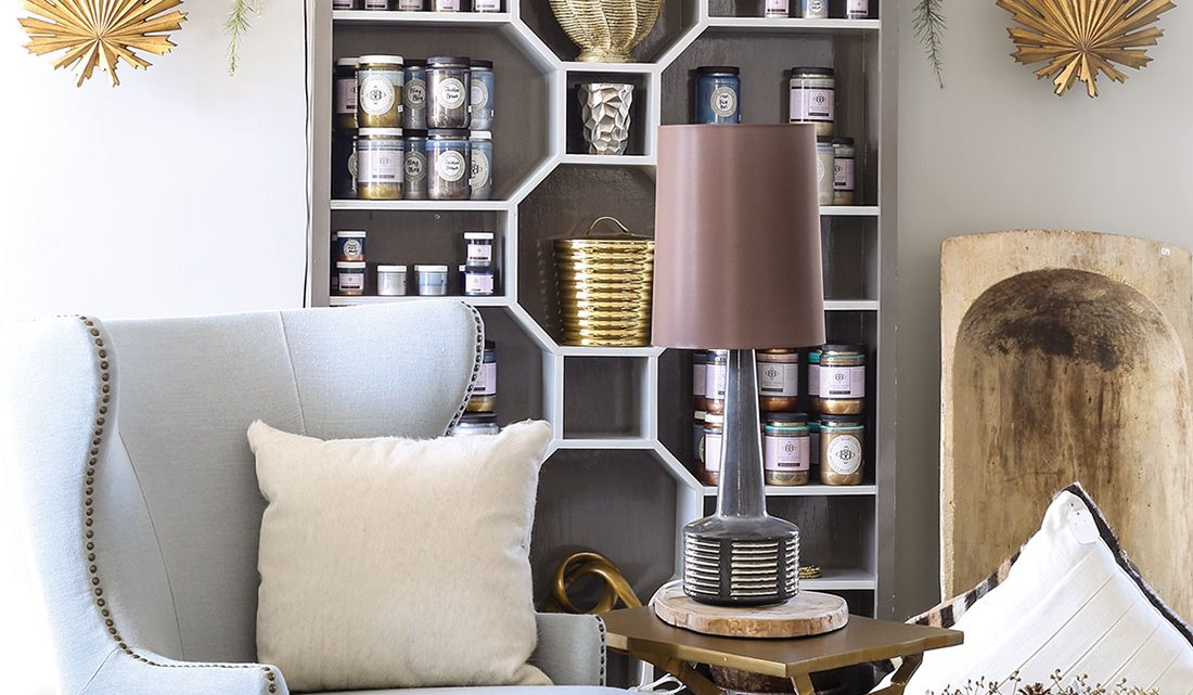 Store scene from Bridget Beari in Richmond, Virginia, includes light blue wing chair, bookcase with the shelves arranged in a geometric pattern, and other unique decor