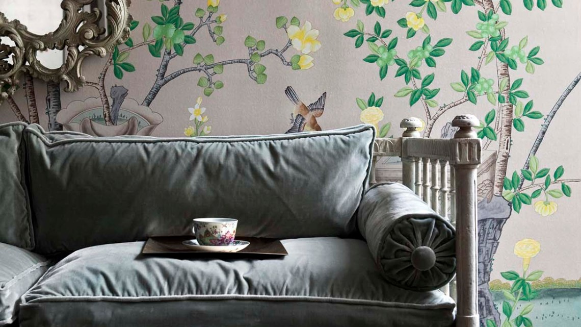 A tea cup and saucer sit on a pale gray velvet sofa, with de Gournay's 'Jardinieres Citrus Trees' on metallic Chinese rice paper on the walls behind it