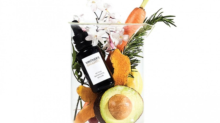 Product shot showing a serum in small dark glass bottle with Vintner's Daughter logo, placed in a glass beaker with some of its ingredients - avocado, carrot, flowers, and herbs.
