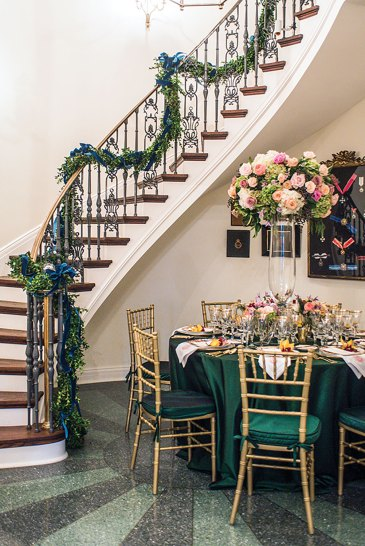 Swags of evergreen garland adorn the banister of the curving staircase that ascends from the rotunda.